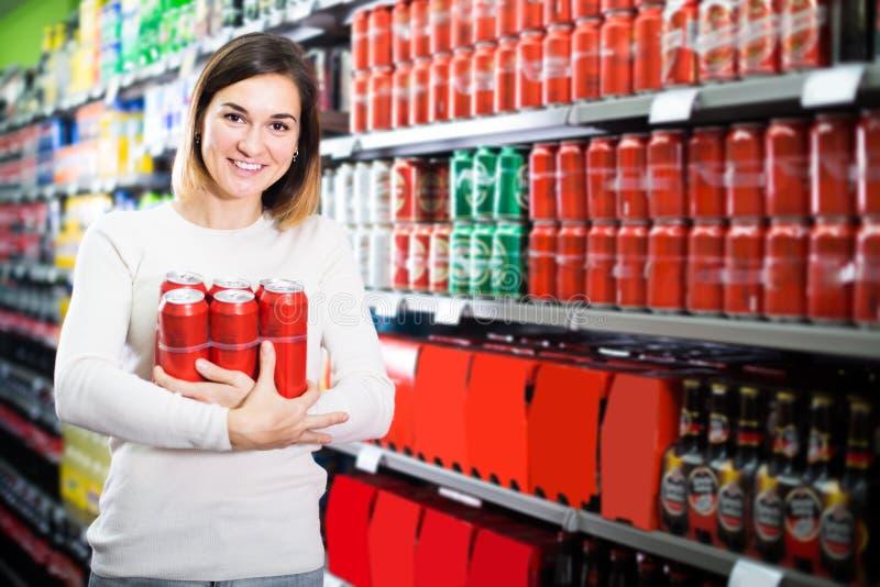 Νέος θηλυκός αγοραστής που ψάχνει για το πακέτο μπύρας στοκ φωτογραφία με δικαίωμα ελεύθερης χρήσης