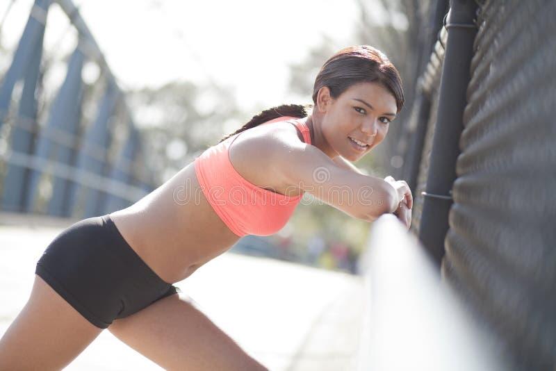 Νέος θηλυκός αθλητής που κλίνει στο κιγκλίδωμα στοκ φωτογραφία με δικαίωμα ελεύθερης χρήσης