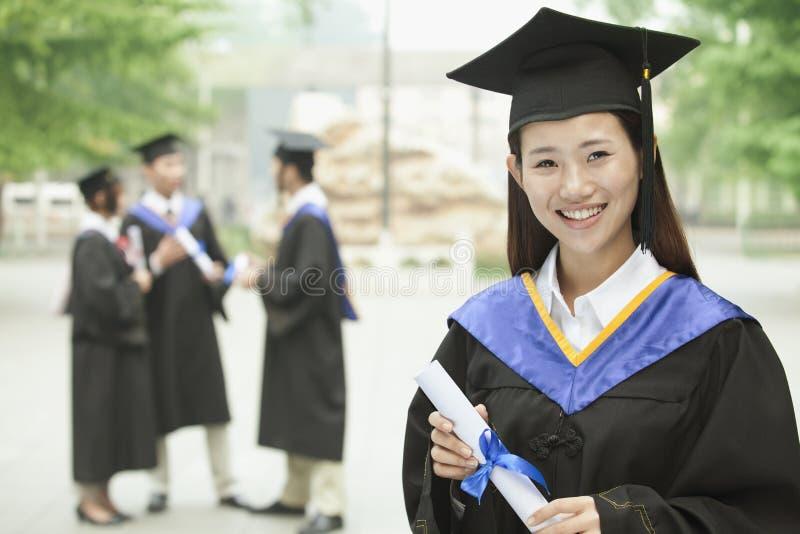 Νέος θηλυκός πανεπιστημιακός πτυχιούχος, πορτρέτο με το δίπλωμα στοκ φωτογραφία με δικαίωμα ελεύθερης χρήσης
