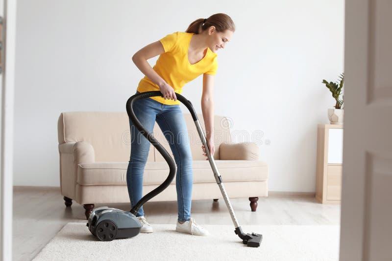 Νέος καθαρίζοντας τάπητας γυναικών με το κενό στοκ φωτογραφίες