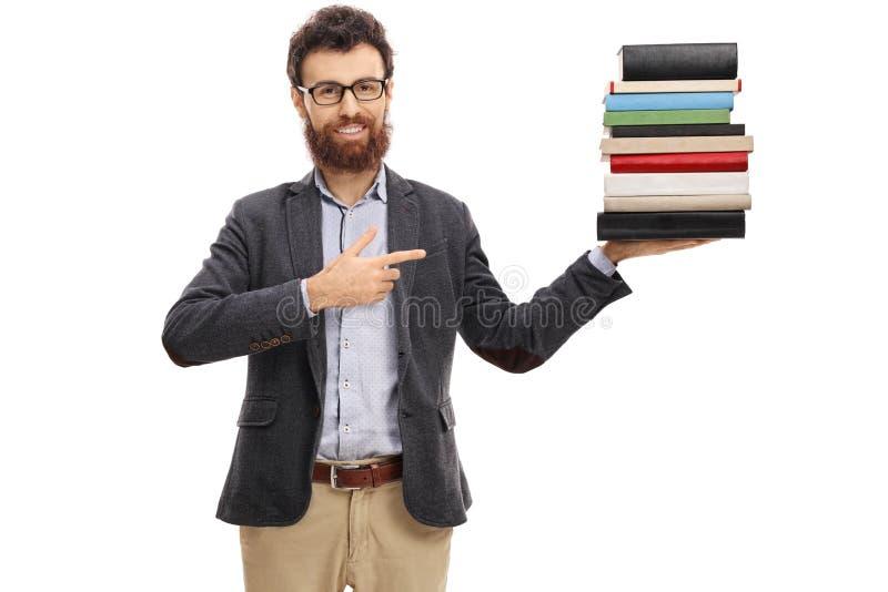 Νέος καθηγητής που κρατά έναν σωρό των βιβλίων και της υπόδειξης στοκ εικόνα