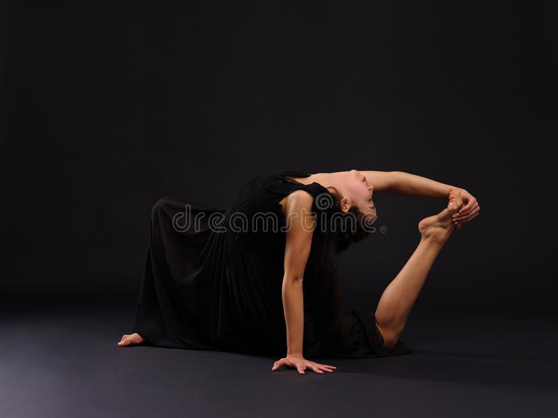 Νέος και ταλαντούχος gymnast κοριτσιών, κάθεται σε ένα γόνατο και κάμπτει πίσω Σε μια μαύρη ανασκόπηση στοκ φωτογραφίες με δικαίωμα ελεύθερης χρήσης