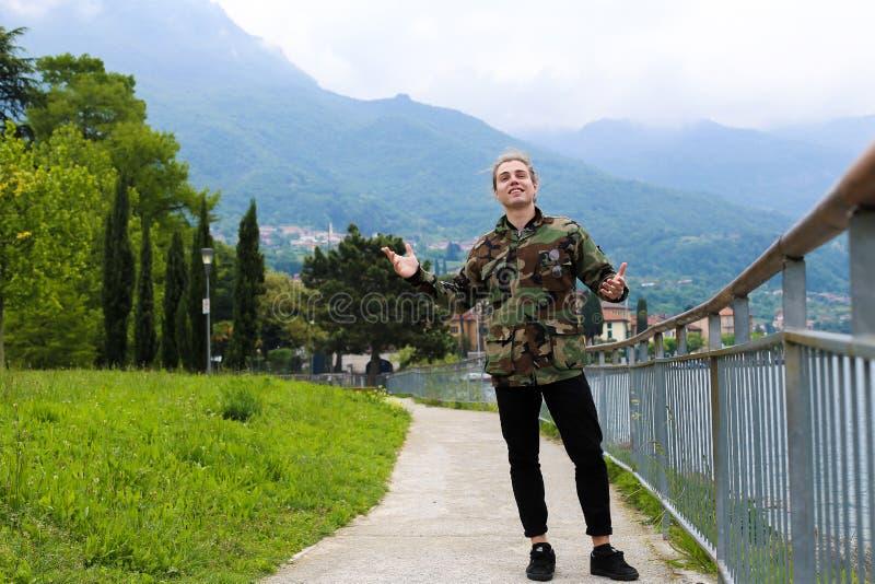 Νέος καυκάσιος αρσενικός τουρίστας που φορά το σακάκι κάλυψης που στέκεται κοντά στη ράμπα, τη λίμνη Como και το βουνό Άλπεων στο στοκ φωτογραφία με δικαίωμα ελεύθερης χρήσης