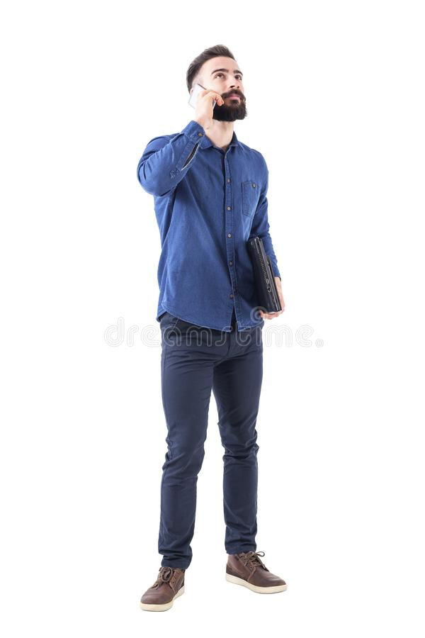 Νέος καυκάσιος επιχειρηματίας στο τηλέφωνο που φαίνεται επάνω φέρνοντας lap-top κάτω από το βραχίονα στοκ φωτογραφία με δικαίωμα ελεύθερης χρήσης