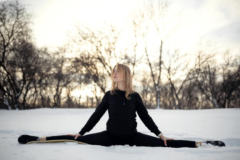 Νέος καυκάσιος θηλυκός ξανθός στις περικνημίδες που τεντώνουν τη συνεδρίαση άσκησης σε μια σειρά σε υπαίθριο στη χιονώδη δασική τ στοκ εικόνα