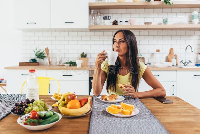 Νέος καφές κατανάλωσης γυναικών στο σπίτι το πρωί στοκ φωτογραφία