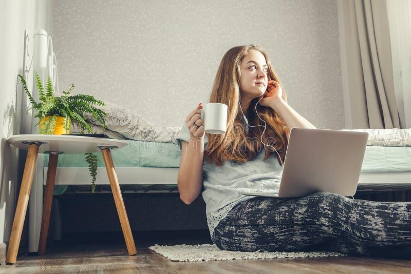 Νέος καφές κατανάλωσης γυναικών χρησιμοποιώντας το lap-top της στην κρεβατοκάμαρα και ακούοντας τη μουσική στοκ φωτογραφία