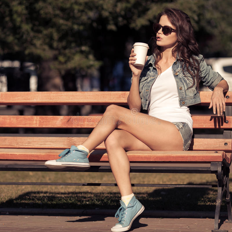 Νέος καφές κατανάλωσης γυναικών από το φλυτζάνι εγγράφου Κάθισμα στον πάγκο στοκ φωτογραφίες με δικαίωμα ελεύθερης χρήσης