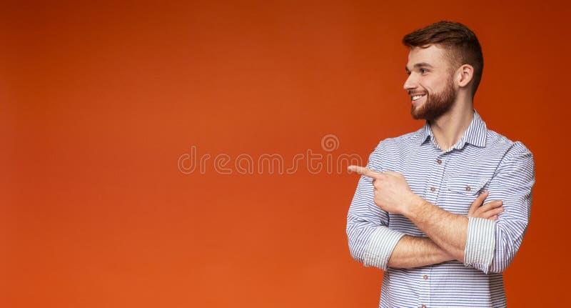 Νέος κοκκινομάλλης τύπος που παρουσιάζει με το δάχτυλο στο διάστημα αντιγράφων στοκ φωτογραφία με δικαίωμα ελεύθερης χρήσης
