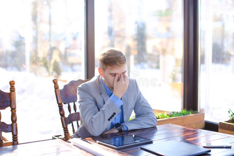 Νέος κουρασμένος διευθυντής που έχει το σπάσιμο στον καφέ με το έγγραφο ρόλων, ταμπλέτα στοκ φωτογραφίες