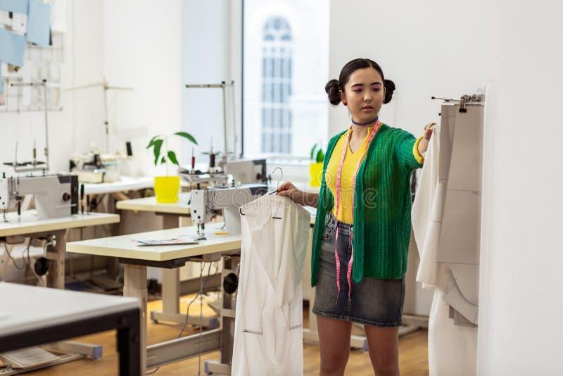 Νέος λεπτός ασιατικός σχεδιαστής μόδας σε μια κοντή φούστα που φαίνεται στοκ εικόνες