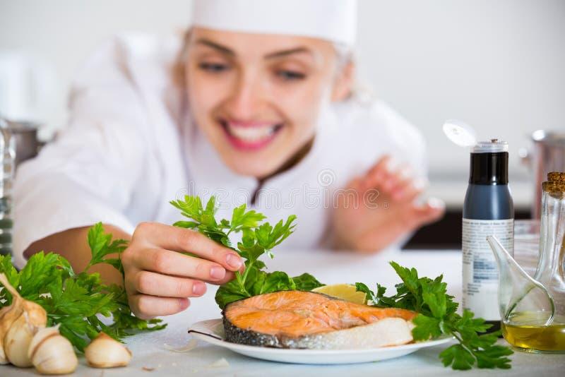 Νέος μάγειρας με τον έτοιμο σολομό στην επαγγελματική κουζίνα στοκ φωτογραφίες