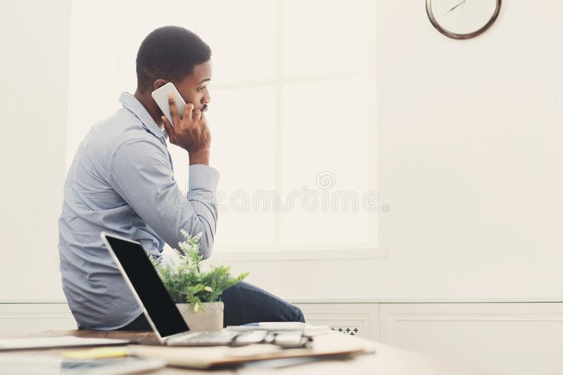 Νέος μαύρος επιχειρηματίας που διοργανώνει την τηλεφωνική συζήτηση στοκ εικόνα