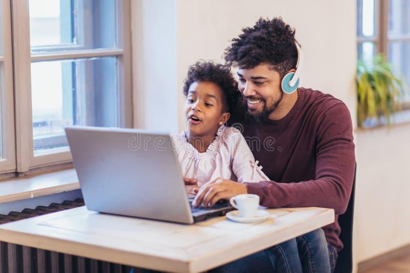 Νέος μαύρος πατέρας που εγκαθιστά μαζί με την κόρη του, που χρησιμοποιεί το lap-top στοκ εικόνα