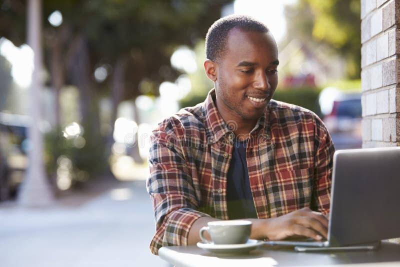Νέος μαύρος που χρησιμοποιεί έναν φορητό προσωπικό υπολογιστή έξω από έναν καφέ στοκ φωτογραφία με δικαίωμα ελεύθερης χρήσης