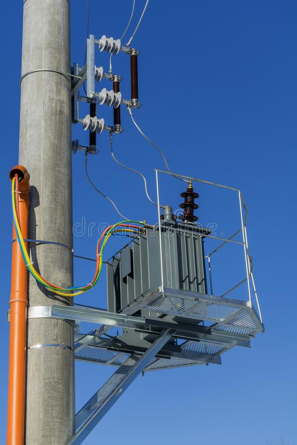 Νέος μετασχηματιστής διανομής στο συγκεκριμένο πόλο δύναμης με τον εξωτερικό ηλεκτρικό διαχωριστή ενάντια στο μπλε ουρανό στοκ φωτογραφία με δικαίωμα ελεύθερης χρήσης