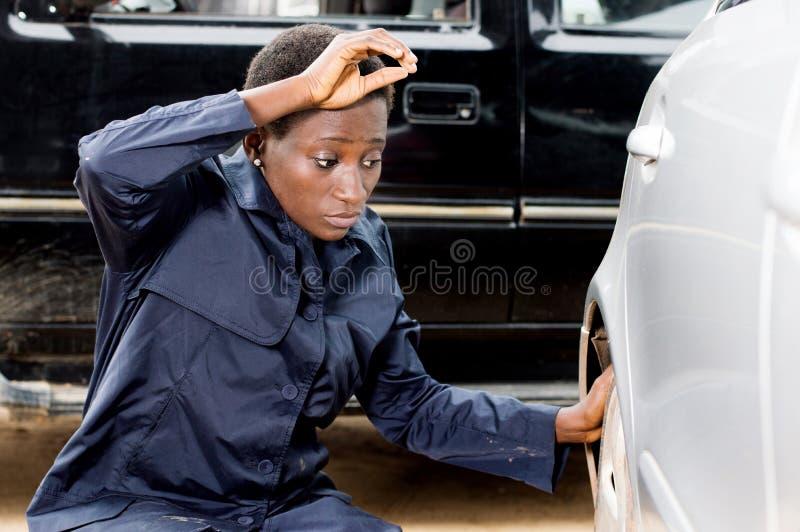 Νέος μηχανικός γυναικών που αλλάζει μια ρόδα ενός αυτοκινήτου στοκ φωτογραφία με δικαίωμα ελεύθερης χρήσης
