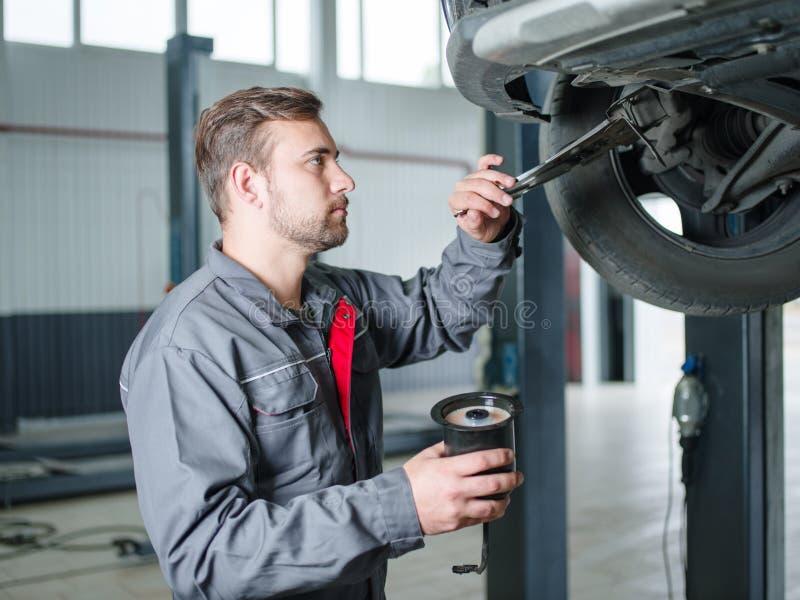 Νέος μηχανικός με ένα εργαλείο διαθέσιμο αντικαθιστώντας μια ρόδα αυτοκινήτων στοκ φωτογραφίες
