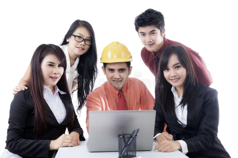 Νέος μηχανικός με τους επιχειρηματίες στο στούντιο στοκ φωτογραφίες
