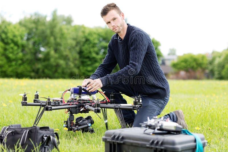 Νέος μηχανικός που προετοιμάζει τον κηφήνα κατασκόπων στο πάρκο στοκ εικόνα