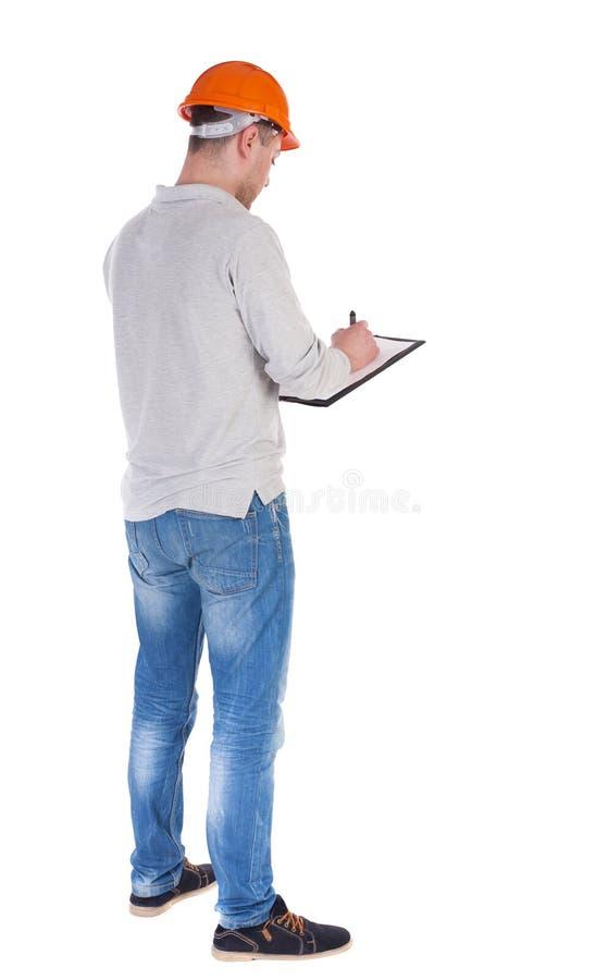 Νέος μηχανικός σε ένα προστατευτικό κράνος με το σημειωματάριο στα χέρια στοκ εικόνα με δικαίωμα ελεύθερης χρήσης