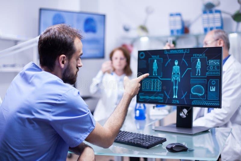 Νέος μηχανικός στο κέντρο inovation για την έρευνα σωμάτων που δείχνει στο όργανο ελέγχου στοκ εικόνα