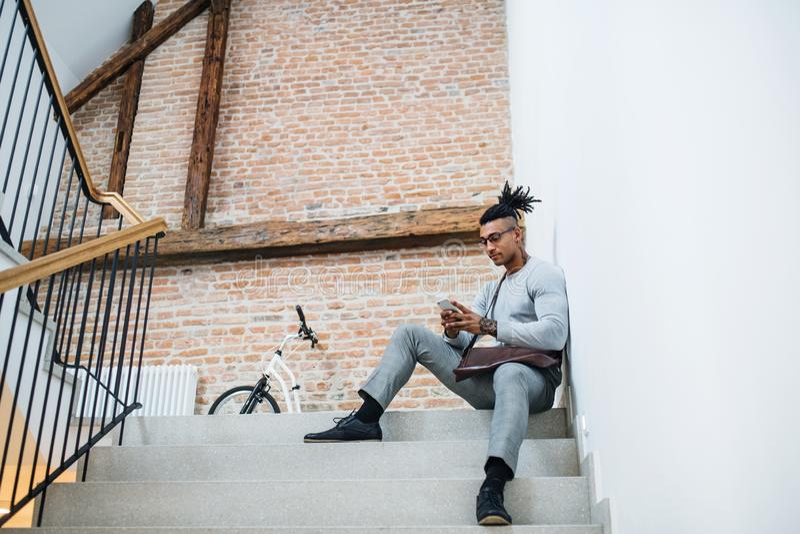 Νέος μικτός επιχειρηματίας φυλών με την τηλεφωνική συνεδρίαση στα σκαλοπάτια στο κτήριο γραφείων στοκ εικόνα με δικαίωμα ελεύθερης χρήσης