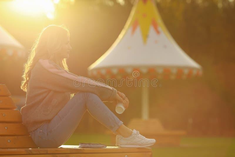 Νέος μοντέρνος καφές κατανάλωσης γυναικών σε ένα πάρκο όμορφο ηλιοβασίλεμα κο&r στοκ εικόνες