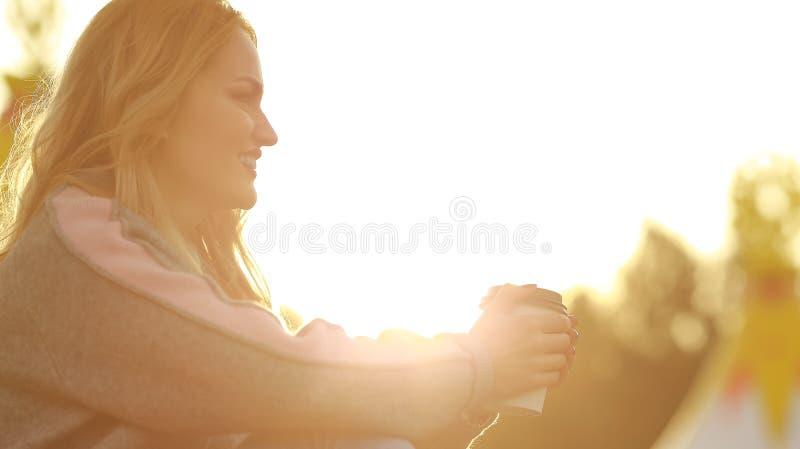 Νέος μοντέρνος καφές κατανάλωσης γυναικών σε ένα πάρκο όμορφο ηλιοβασίλεμα κο&r στοκ εικόνες με δικαίωμα ελεύθερης χρήσης
