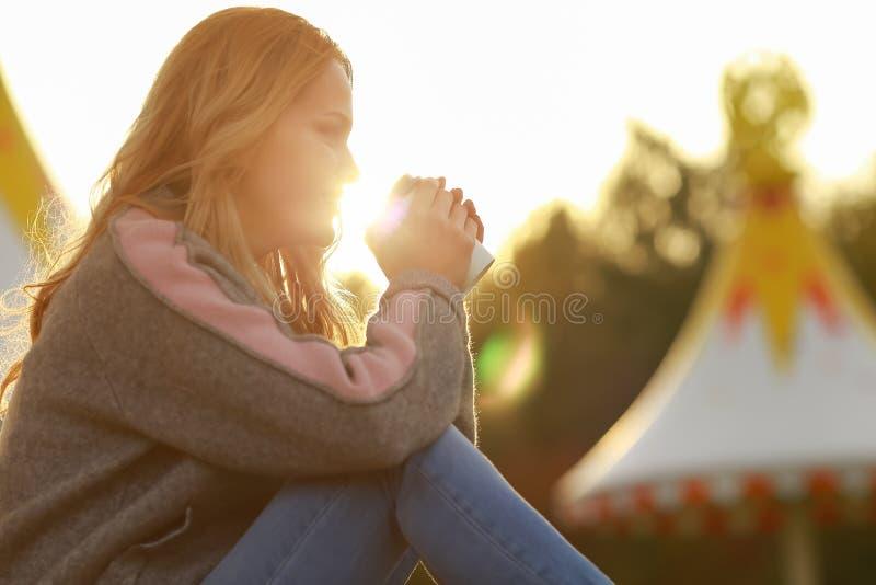 Νέος μοντέρνος καφές κατανάλωσης γυναικών σε ένα πάρκο όμορφο ηλιοβασίλεμα κο&r στοκ εικόνα με δικαίωμα ελεύθερης χρήσης
