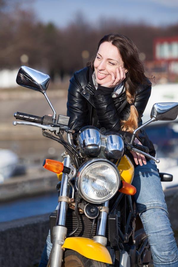 Νέος μοτοσυκλετιστής γυναικών που τίθεται έξω tonque σε κάποιο στοκ εικόνες με δικαίωμα ελεύθερης χρήσης