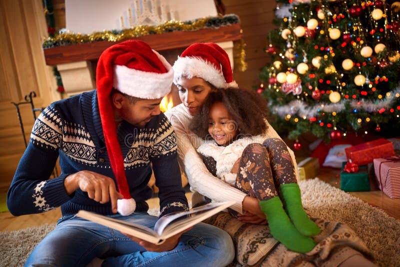Νέος μπαμπάς που διαβάζει ένα βιβλίο στη χαριτωμένη κόρη κοντά στο χριστουγεννιάτικο δέντρο στοκ φωτογραφία με δικαίωμα ελεύθερης χρήσης