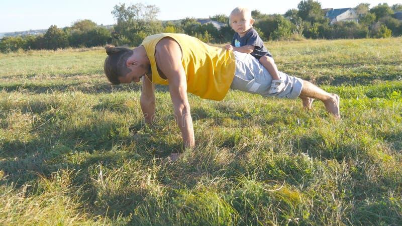 Νέος μυϊκός πατέρας που κάνει την ώθηση UPS με το μικρό γιο του στην πλάτη του Αθλητικό άτομο που κάνει το ώθηση-UPS στην πράσινη στοκ εικόνες με δικαίωμα ελεύθερης χρήσης