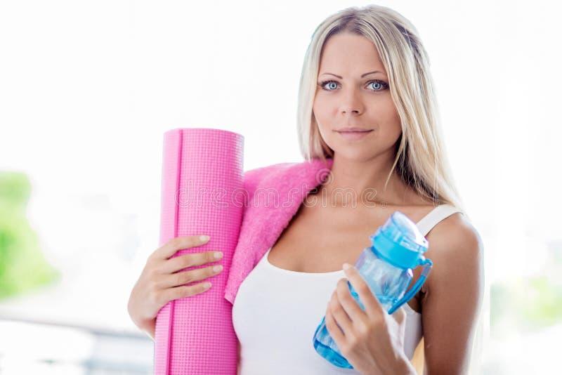 Νέος ξανθός αθλητισμός ικανότητας γυναικών πηγαίνοντας με την πετσέτα, μπουκάλι του wat στοκ εικόνες με δικαίωμα ελεύθερης χρήσης
