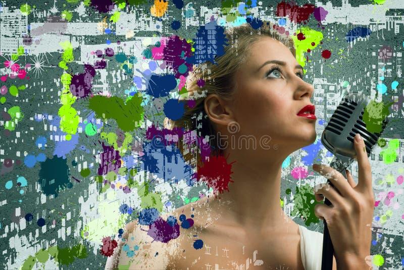 Νέος ξανθός θηλυκός τραγουδιστής με το μικρόφωνο στοκ εικόνες