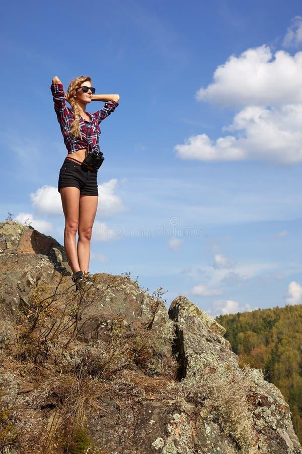 Νέος ξανθός τουρίστας γυναικών στο πουκάμισο και σορτς σε έναν απότομο βράχο στο β στοκ φωτογραφία με δικαίωμα ελεύθερης χρήσης