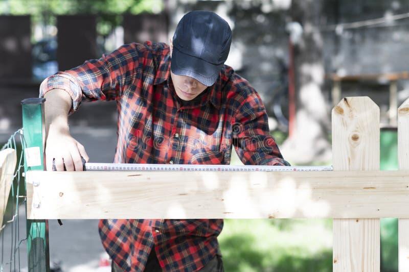 Νέος ξυλουργός που μετρά το ξύλο που χρησιμοποιεί ένα μέτρο ταινιών στον κήπο στοκ εικόνα με δικαίωμα ελεύθερης χρήσης