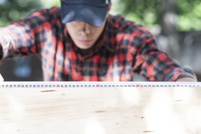 Νέος ξυλουργός που μετρά το ξύλο που χρησιμοποιεί ένα μέτρο ταινιών στον κήπο στοκ εικόνες με δικαίωμα ελεύθερης χρήσης