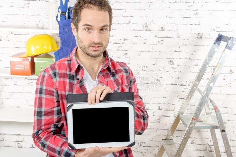 Νέος ξυλουργός που παρουσιάζει οθόνη στην ψηφιακή ταμπλέτα στοκ φωτογραφίες
