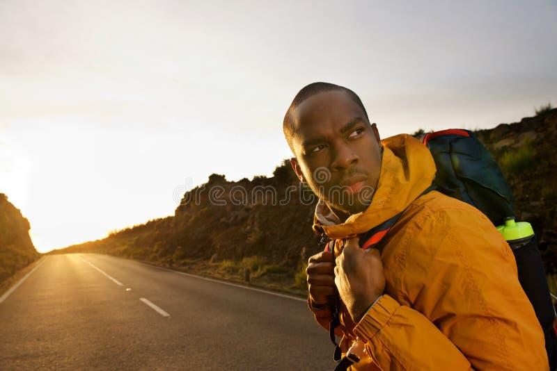 Νέος οδοιπόρος αφροαμερικάνων που περπατά στο δρόμο με το σακίδιο πλάτης κατά τη διάρκεια του ηλιοβασιλέματος και που γυρίζει γύρ στοκ φωτογραφία με δικαίωμα ελεύθερης χρήσης