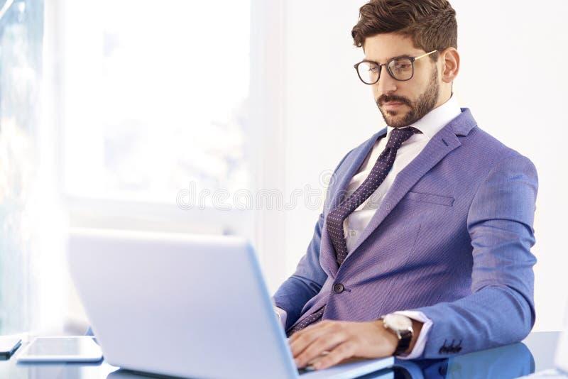 Νέος οικονομικός επιχειρηματίας συμβούλων που χρησιμοποιεί το σημειωματάριο ενώ εργασία στοκ φωτογραφία
