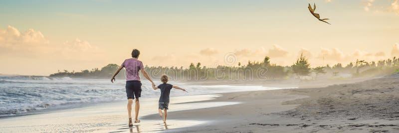 Νέος πατέρας και ο γιος του που τρέχουν με τον ικτίνο στο ΕΜΒΛΗΜΑ παραλιών, ΜΑΚΡΟΧΡΟΝΙΟ ΣΧΗΜΑ στοκ φωτογραφία
