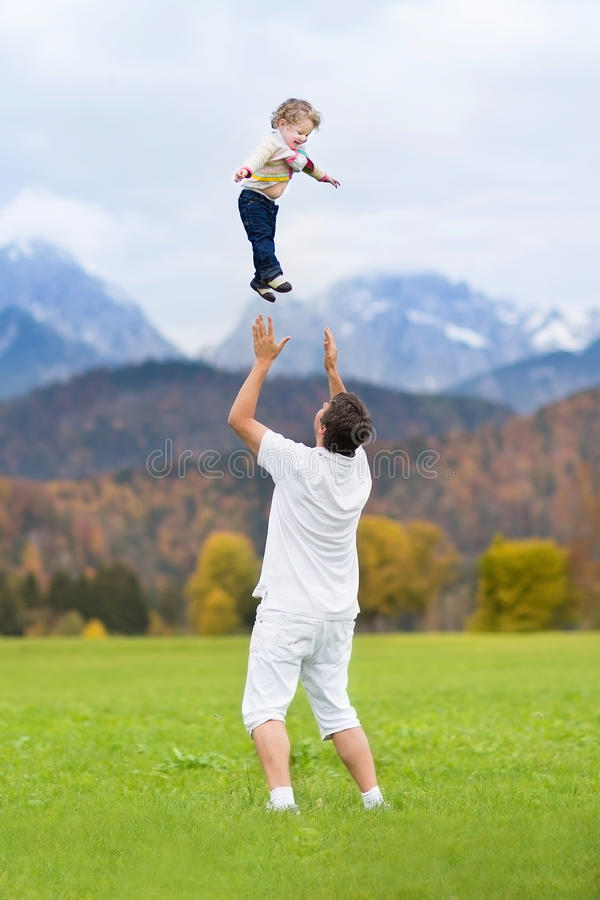 Νέος πατέρας που ρίχνει το μωρό του υψηλό στον ουρανό στοκ εικόνες