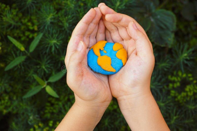 Νέος πλανήτης Γη εκμετάλλευσης αγοριών στα χέρια του στοκ εικόνα με δικαίωμα ελεύθερης χρήσης