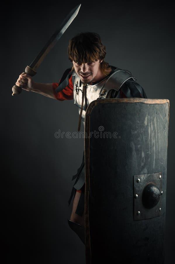 Νέος πολεμιστής με ένα ξίφος και μια ασπίδα υπό εξέταση στοκ φωτογραφία
