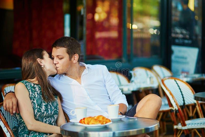 Νέος ρομαντικός καφές κατανάλωσης ζευγών σε έναν άνετο υπαίθριο καφέ στο Παρίσι, Γαλλία στοκ φωτογραφία