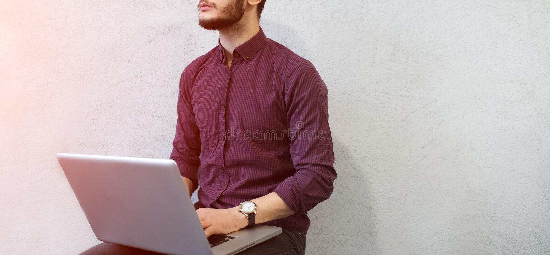 Νέος σκεπτικός τύπος που χρησιμοποιεί το lap-top, που φορά τα γυαλιά στο υπόβαθρο του λευκού στοκ εικόνες