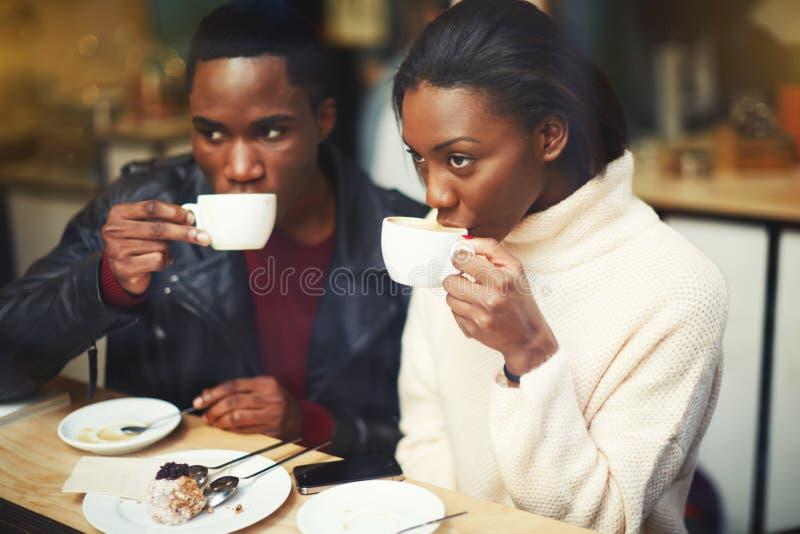 Νέος σκοτεινός ξεφλουδισμένος καφές κατανάλωσης ανδρών και γυναικών καθμένος μαζί στο σύγχρονο καφέ στην κρύα χειμερινή ημέρα στοκ εικόνα με δικαίωμα ελεύθερης χρήσης