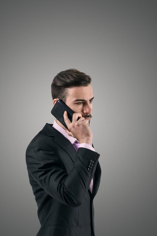 Νέος σοβαρός επιχειρηματίας που μιλά στο κινητό τηλέφωνο στοκ φωτογραφία με δικαίωμα ελεύθερης χρήσης