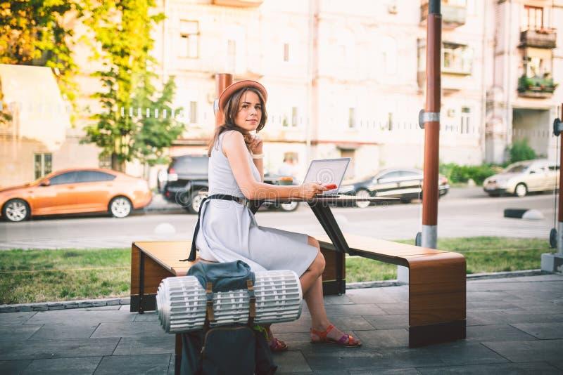Νέος σπουδαστής τουρισμού και ταξιδιού θέματος το όμορφο νέο καυκάσιο κορίτσι στο φόρεμα και το καπέλο κάθεται στον καφέ οδών στη στοκ φωτογραφίες με δικαίωμα ελεύθερης χρήσης